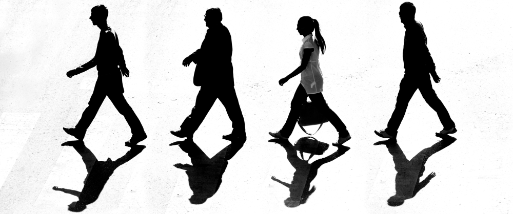 Black and white image of business professionals walking across a street