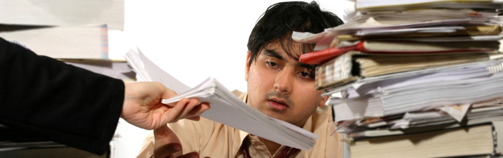 A frustrated employee surrounded by piles of paper being handed a stack of papers by another employee