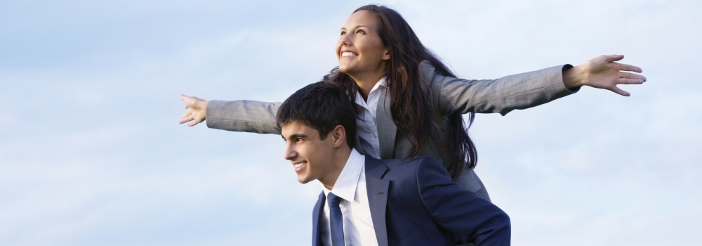 a male business professional with a female business professional on his back, piggy-back style.